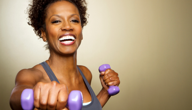 smiling-woman-holding-purple-dumbbells